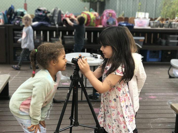 Preschool girls play with camera