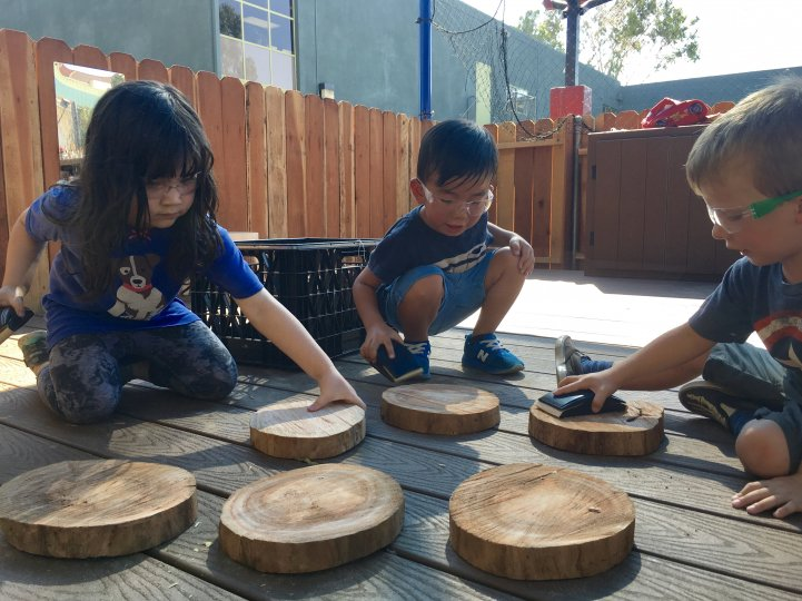 Preschool kids woodwork outdoors