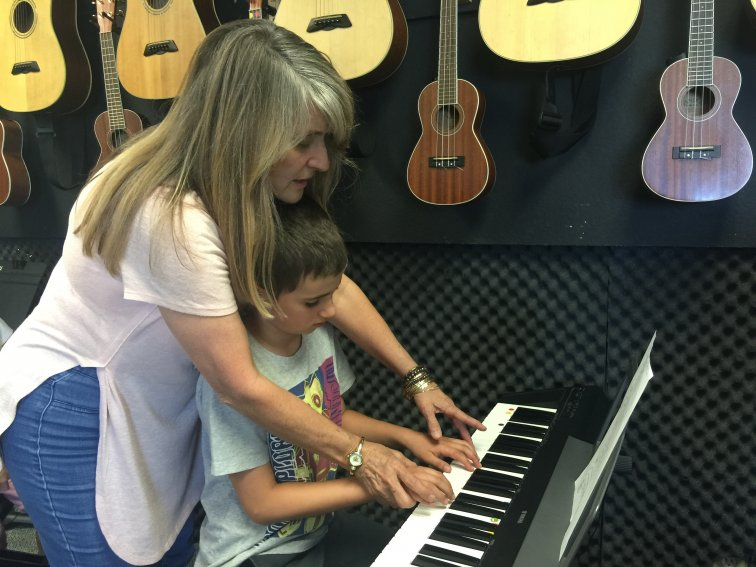 Music Josie teaches student keyboard