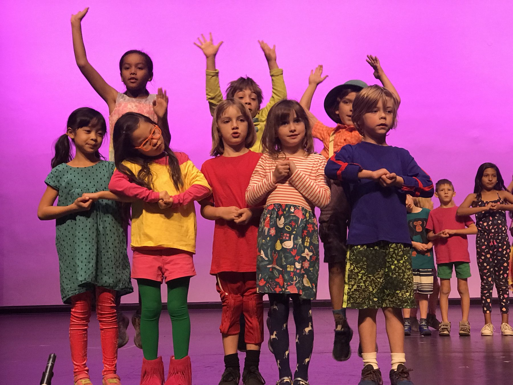 Stage performance ES kids in colorful costumes