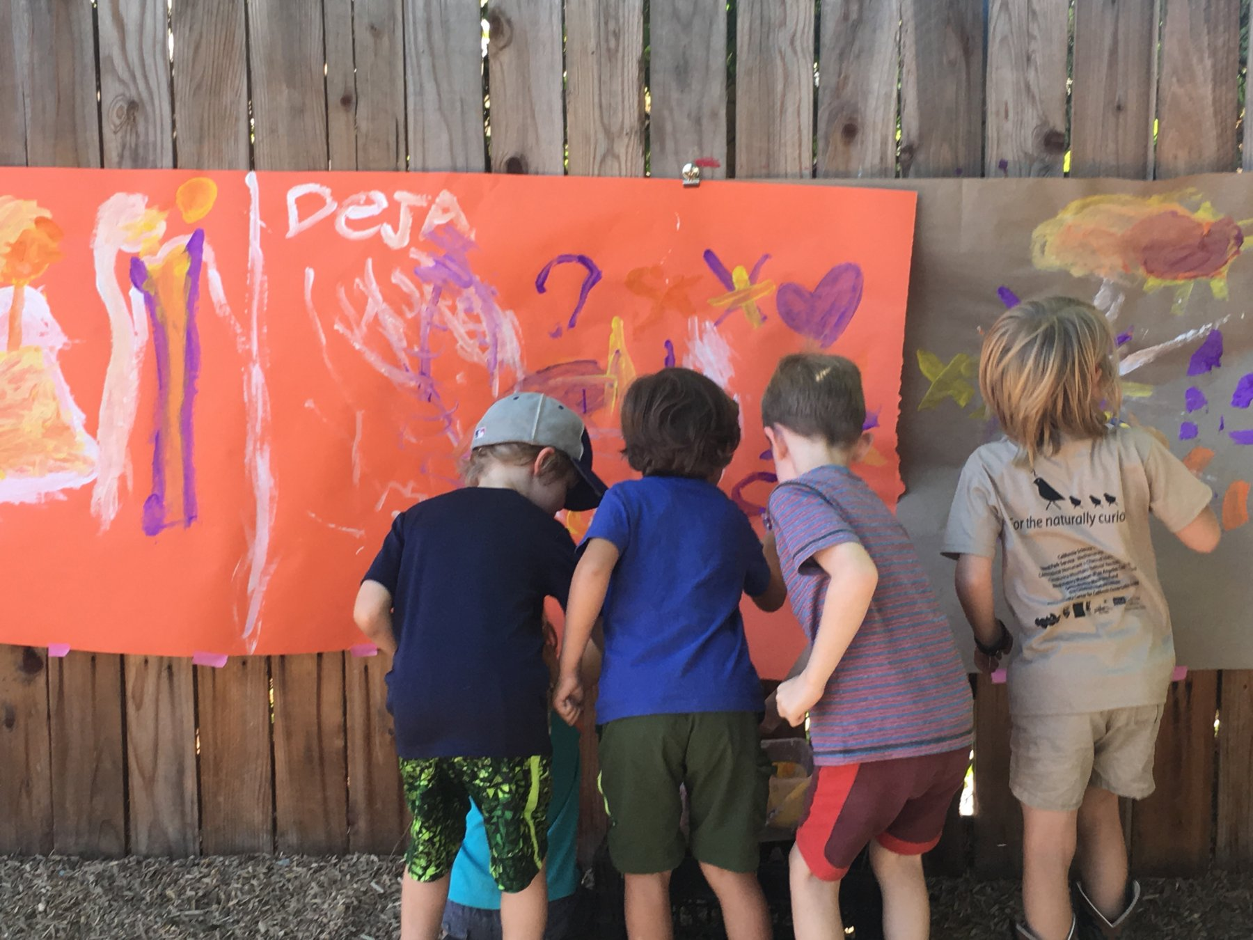 ES Boys in yard painting on butcher paper
