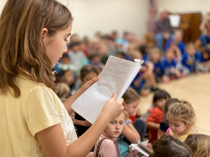 ES girl reads at all school meeting
