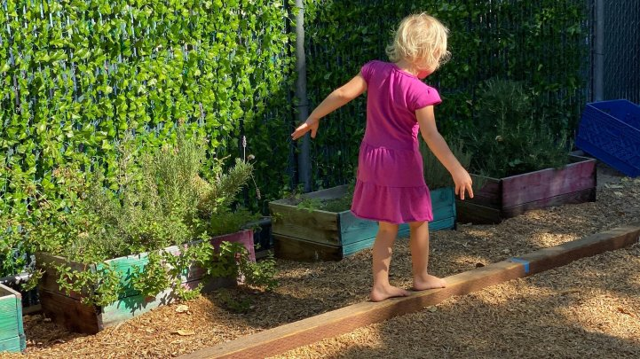 Preschool girl balances on beam
