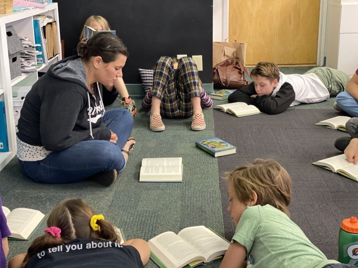 ES Molly with students reading on rug