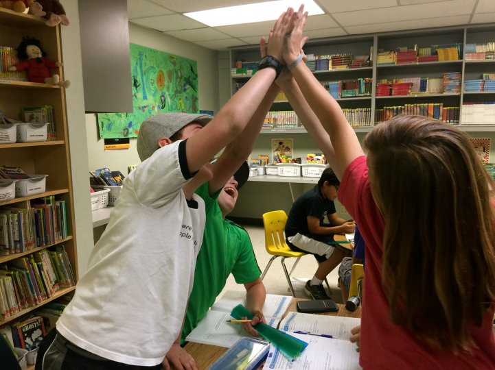 ES kids high five in library