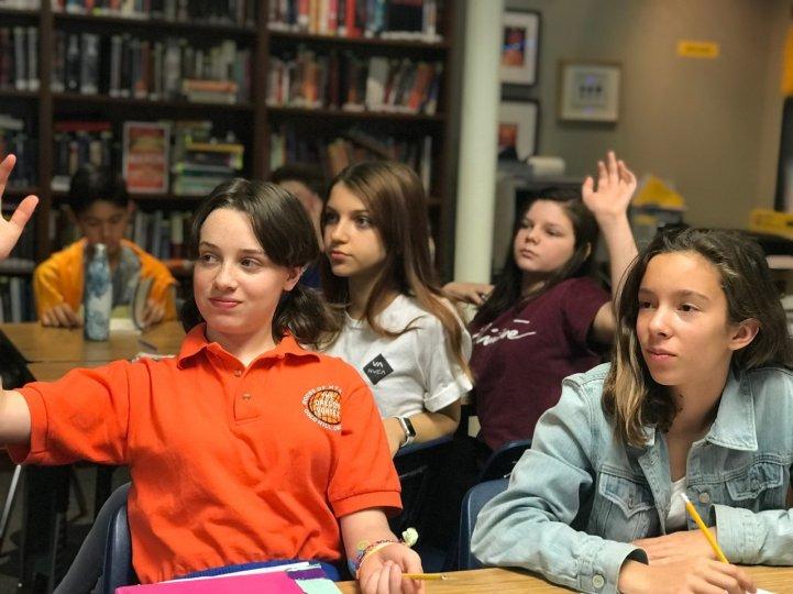 MS Girls in classroom raising hands